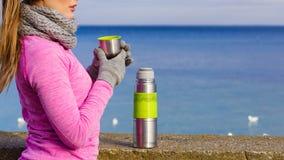 De geschikte vrouw in het koude dag opwarmen drinkt thee stock afbeelding