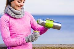 De geschikte vrouw in het koude dag opwarmen drinkt thee royalty-vrije stock foto's