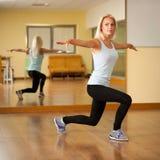 De geschikte vrouw werkt in gymnastiek uit die stap maken uitvallen Royalty-vrije Stock Foto