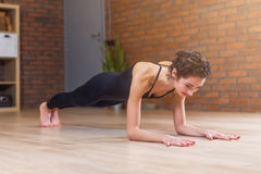De geschikte vrouw yoga doen of pilates de oefening die zich in plank bevinden stelt geroepen phalankasana uitwerkend op vloer in royalty-vrije stock fotografie