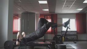 De geschiktheidsmens ligt op de bank en heft zijn benen op Kernkruis die uitwerkend abs spieren opleiden stock video