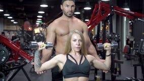 De geschiktheidsvrouw en de jonge trainerman oefenen spieren met domoren in gymnastiek uit stock videobeelden