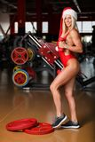 De geschiktheidsvrouw, van gemiddelde lengte, in een rood zwempak, die een Kerstmanhoed dragen, bevindt zich in gymnastiek het st stock fotografie