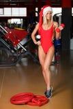 De geschiktheidsvrouw, van gemiddelde lengte, in een rood zwempak, die een Kerstmanhoed dragen, bevindt zich in gymnastiek het st stock afbeeldingen
