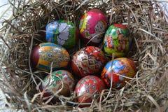 De geschilderde kippeneieren zijn in het nest stock foto's