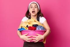 De geschokte bezige Europese vrouw houdt bassin met schone kleren, houdt mond geopend wijd, voorbereidingen treft voor was, draag stock foto's