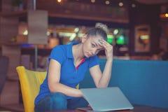 De geschokte en gefrustreerde jonge leuke advocaat bekijkt het scherm van haar laptop Slechte stemming royalty-vrije stock fotografie