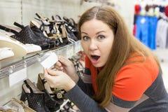 De geschokte Europese vrouw met verbaasd kijkt holdingsmarkering met hoge prijs op schoenen royalty-vrije stock afbeelding