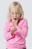 De geschokte jonge muntstukken van de meisjesholding over witte achtergrond royalty-vrije stock foto