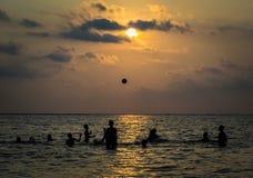 De gesilhouetteerde groep jongen speelt een bal in het overzees stock afbeelding