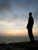 De gesilhouetteerde jonge mens let op zonsopgang van een pijler. stock fotografie