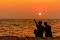 De gesilhouetteerde paarzitting, en ontspant op strand in liefde en omhelst, zonsondergang in het strand stock afbeeldingen
