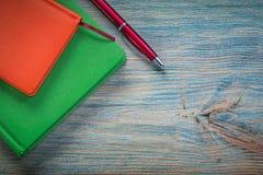 De gesloten ballpoint van notaboeken op uitstekend houten raadsbureau bedriegt Stock Afbeeldingen