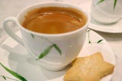 De gesloten omhoog hete koffie in een witte kop met een vage ster vormde koekje royalty-vrije stock foto's