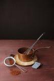 De gesmolten chocolade in pan met zwaait op de houten achtergrond Stock Foto's