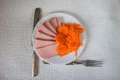 De gesneden ham met wortelen is in de plaat stock fotografie