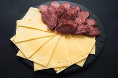 De gesneden kaas en salamiworst ligt op een ronde steen zwarte raad Kaasplakken op een zwarte achtergrond Worst op een ronde word stock foto's