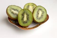 De gesneden kiwivruchten liggen op een schotel stock afbeelding