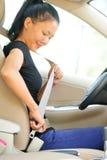 De gesp van de vrouwenbestuurder omhoog de veiligheidsgordel in auto Stock Fotografie
