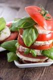 De gestapelde Plakken van de Tomaat en van de Mozarella Stock Foto