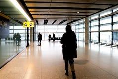 De gestileerde mening van het loneyeind van een terminal in een luchthaven met de onherkenbare silhouetten van enkelen bundelde p stock foto's