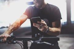 De getatoeeerde gebaarde spiermens in holdingssmartphone handen en het gebruiken brengt app in kaart alvorens door elektrische au stock foto