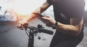 De getatoeeerde hipster mens in holdingssmartphone handen en het gebruiken brengt app in kaart alvorens door elektrische autoped  stock afbeelding