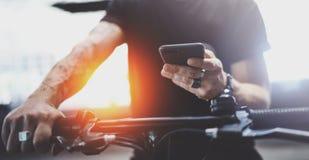 De getatoeeerde hipster mens in holdingssmartphone handen en het gebruiken brengt app in kaart alvorens door elektrische autoped  stock afbeeldingen