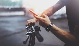 De getatoeeerde hipster mens in holdingssmartphone handen en het gebruiken brengt app in kaart alvorens door elektrische autoped  royalty-vrije stock afbeeldingen