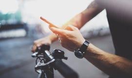 De getatoeeerde hipster mens in holdingssmartphone handen en het gebruiken brengt app in kaart alvorens door elektrische autoped  stock foto's