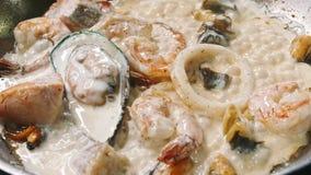 De geurige garnalen, de mosselen en de vissen zijn gebraden in een steelpan in een pan in langzame motie in 4k-resolutie stock footage