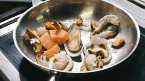 De geurige garnalen, de mosselen en de vissen zijn gebraden in een steelpan in een pan in langzame motie in 4k-resolutie stock video