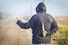 De gevaarlijke mens op de weg met een mes probeert einde de auto Stock Afbeeldingen
