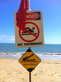 De gevaarssinus op strand geen zwemmend krokodillenstrand sloot de krokodil van het eindegevaar in water Stock Afbeelding