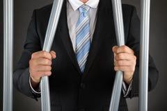 De Gevangenis van zakenmanbending bars of royalty-vrije stock foto