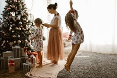 De gevende moeder vlecht haar de vlecht van weinig dochter terwijl de tweede dochter de boom van een Nieuwjaar in het comfortabel royalty-vrije stock afbeelding
