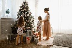 De gevende moeder vlecht haar de vlecht van weinig dochter terwijl de tweede dochter de boom van een Nieuwjaar in het comfortabel royalty-vrije stock foto
