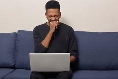 De gevilde foto van vermoeide donker voelt moeheid van het werk aangaande laptop computer, geeuwen en wil slapen, gekleed in zwar stock foto's