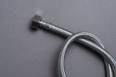 De gevlechte slang van het roestvrij staalwater over grijze achtergrond Stock Foto's