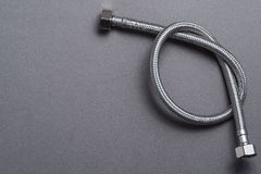 De gevlechte slang van het roestvrij staalwater over grijze achtergrond Royalty-vrije Stock Afbeeldingen