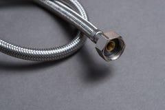 De gevlechte slang van het roestvrij staalwater over grijze achtergrond Royalty-vrije Stock Foto