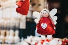 De gevoelde rode en witte decoratie van de engelenkerstboom op verkoop bij een Kerstmismarkt stock afbeeldingen