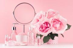 De gevoelige meisjesachtige toilettafel met boeket van rozen, ronde spiegel, cosmetischee producten voor lichaam en huid geeft in stock foto