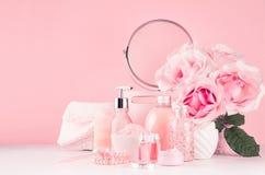 De gevoelige meisjesachtige toilettafel met boeket van rozen, ronde spiegel, cosmetischee producten voor lichaam en huid geeft in stock afbeelding