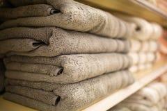 De gevouwen grijze handdoeken op de plank maken loundry schoon stock foto's