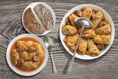 De gevulde die Broodjes van het Koolvlees in Roestvrije die saus-Pot worden gekookt en in Porseleinplaat worden gediend op Oude T Stock Foto's