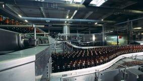 De gevulde en lege glasflessen bewegen zich langs de industriële vervoerder stock videobeelden