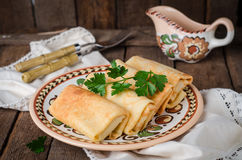 De gevulde Russische pannekoeken rolt met vlees in traditionele kleikom op houten achtergrond Gestemd beeld Selectieve nadruk Stock Afbeelding