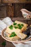 De gevulde Russische pannekoeken rolt met vlees in traditionele kleikom op houten achtergrond Gestemd beeld Selectieve nadruk Stock Afbeeldingen