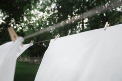 De gewassen handdoeken hangen op de kabel Het linnen is droog Wasknijper op een handdoek die droog is Drogend linnen in de tuin royalty-vrije stock foto